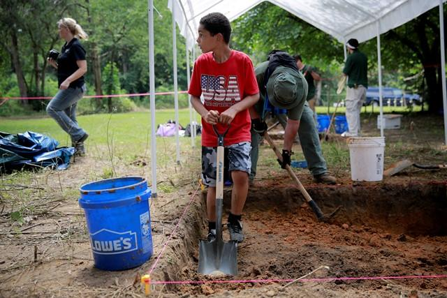 Jason Due-Barnes, 9, helps exhume a grave at the Boot Hill cemetery Saturday.