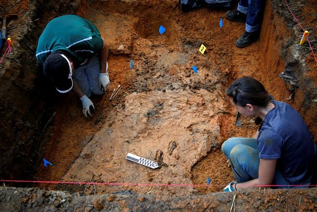 Exhumation work continues in the Boot Hill cemetery Sunday.