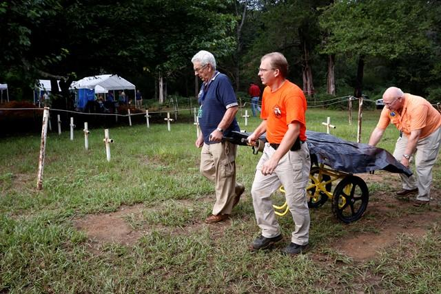 Pat Brewer (from l-r), Jason Byrd, & Larry Bedore, all of the Florida Emergency Mortuary Operations Response System, wheel the first remains to be removed from the Boot Hill cemetery.