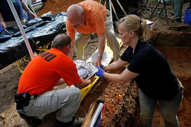 Jason Byrd (from l-r) & Larry Bedores, both with the Florida Emergency Mortuary Operations Response System, help Dr. Kimmerle load remains exhumed from a Boot Hill cemetery grave.