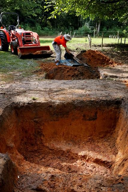 Jason Byrd clears dirt from a tarp while refilling a hole dug to exhume human remains from a grave at the Dozier School for Boys Tuesday.