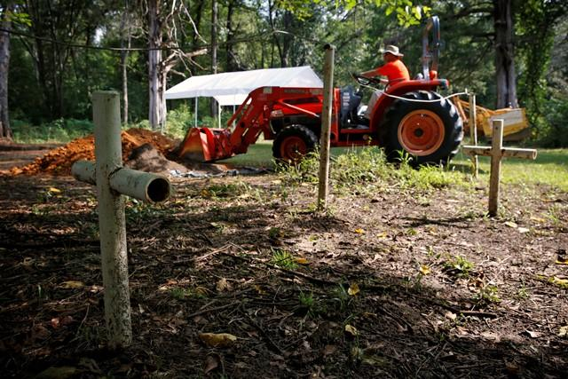 Jason Byrd, Commander of the Florida Emergency Mortuary Operations Response System, uses a front-end loader to refill a hole dug to exhume human remains from a Boot Hill cemetery grave at the Dozier School for Boys Tuesday.