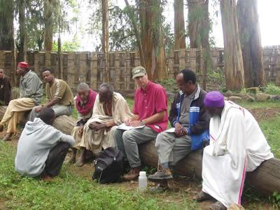John Arthur (center, in green hat) talks to members of the Gamo in Ethiopia.