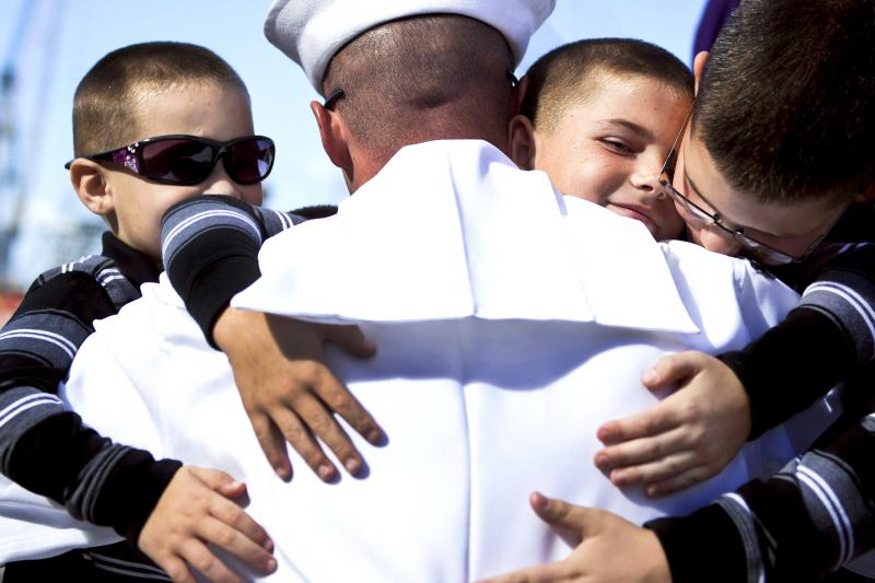 Navy Petty Officer Engineman 1st Class Kevin Ives, assigned to the guided-missile cruiser USS Princeton, embraces his sons during a homecoming celebration on Naval Base San Diego, Oct. 29, 2013.