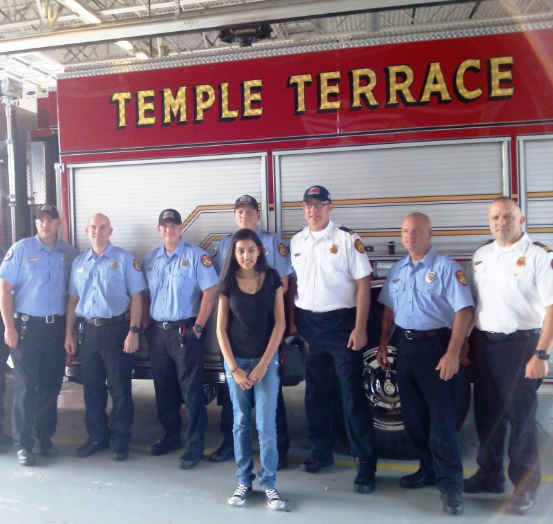 USF student Vaneesha Patel (center) poses with Temple Terrace firefighters after cooking them lunch, one of the 22 random acts of kindness she performed on her 22nd birthday