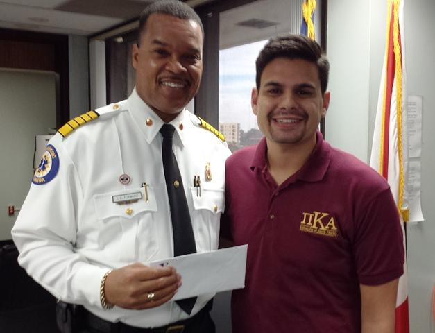 Tampa Fire Rescue Chief Tom Forward & Pi Kappa Alpha external VP Jordan Romero with the check for more than $8600 raised by the Fireman's Challenge