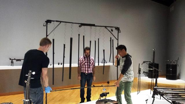Reyes watches as USF Contemporary Art Museum employees move 'pipes' made out of various lengths of sawed-off gun barrels