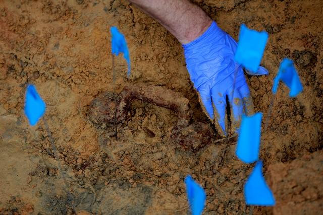 Christian Wells cleans away dirt from a coffin handle during the dig in September