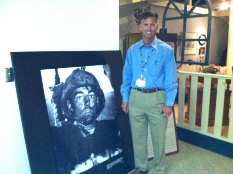 Retired Major Scott Macksam stands next to the photograph of a WWII Marine that motivated him to bring the exhibit to the Tampa Bay area.