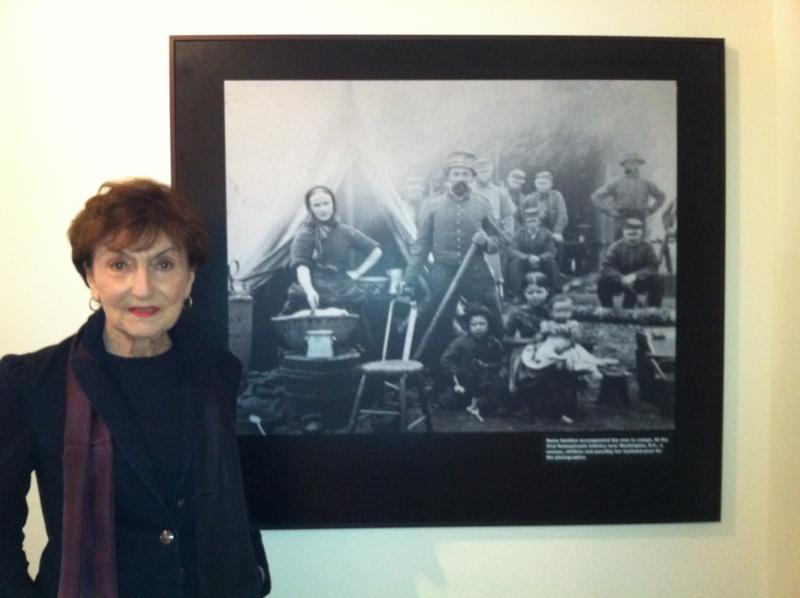 Exhibit curator Cyma Rubin next to the Civil War photo showing a family at a Union campsite.