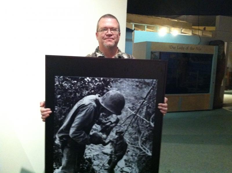 Nevin Sitler, education director at the St. Petersburg Museum of History, holds the photo that shows his wife's grandfather with an infant survivor from a Japanese island where the soldiers and families committed suicide rather than be captured.
