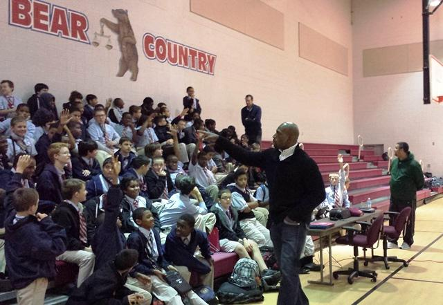"""WWE pro wrestler """"Titus O'Neil"""" (former Univ. of Florida/Tampa Bay Storm football player Thaddeus Bullard) talks to a group of students in Franklin's gymnasium."""