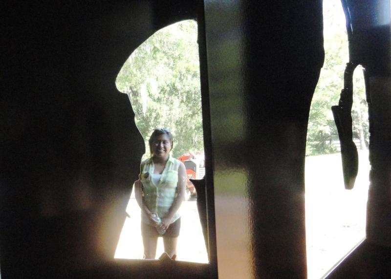 A view of artist Maria Vazquez through the steel silhouette of a member of service.