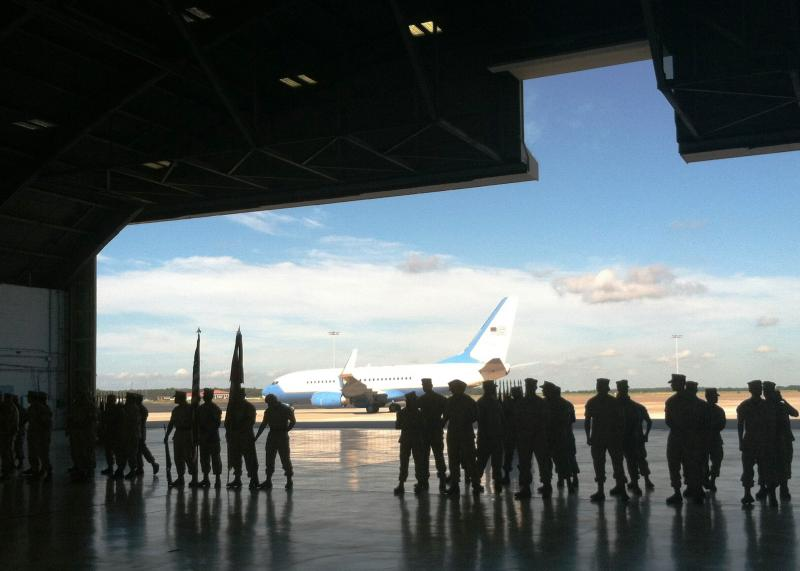 The aircraft that carried top military leaders to the change of command ceremony is framed by silhouettes of Marines waiting for the ceremony to begin.