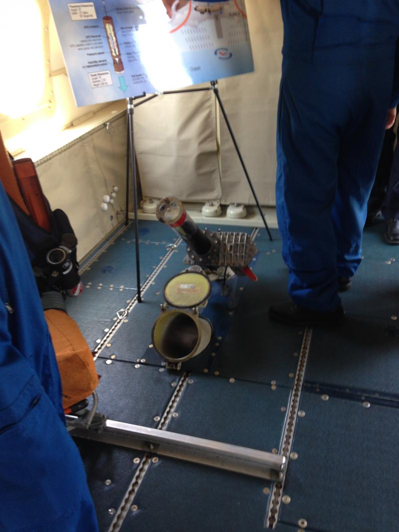 Dropsonde sensors are dropped at a rapid pace through a shoot on the hurricane hunter floor.