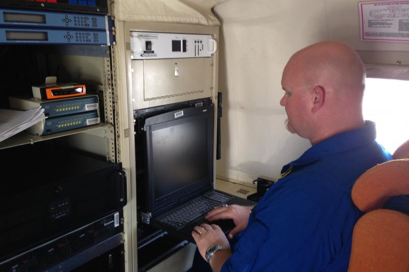 Data technician Todd Richards spends much of a 10-hour mission at his hurricane hunter work station.
