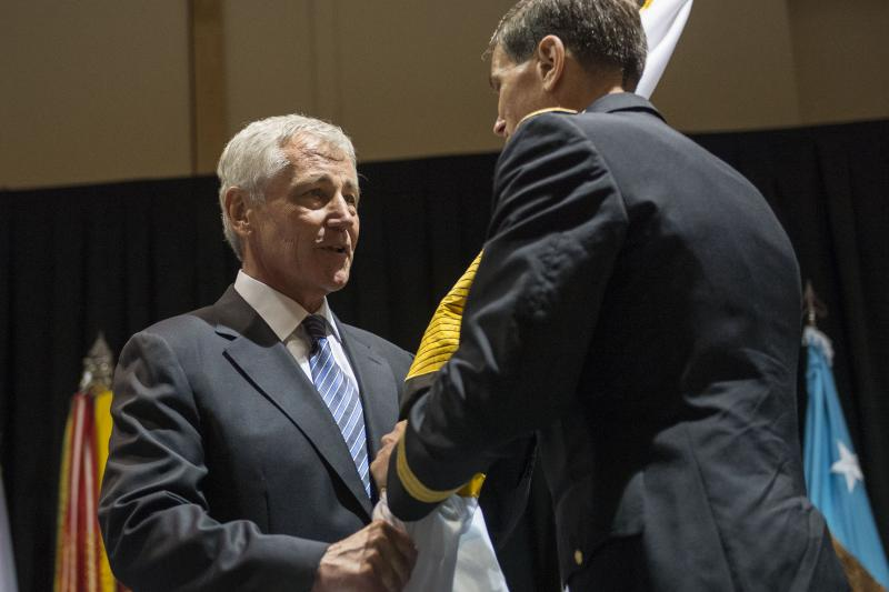 Defense Secretary Chuck Hagel, left, passes the U.S. Special Operations Command flag to incoming commander Army Gen. Joseph L. Votel III during a change-of-command ceremony in Tampa on Aug. 28.
