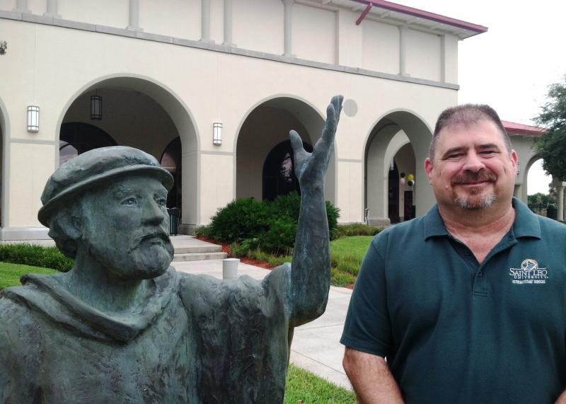"Standing next to the 'teacher statue at Saint Leo Unviersity is Tedd ""Gunny"" Weiser, a retired Marine gunnery sergeant and interim director of Veteran Student Services."