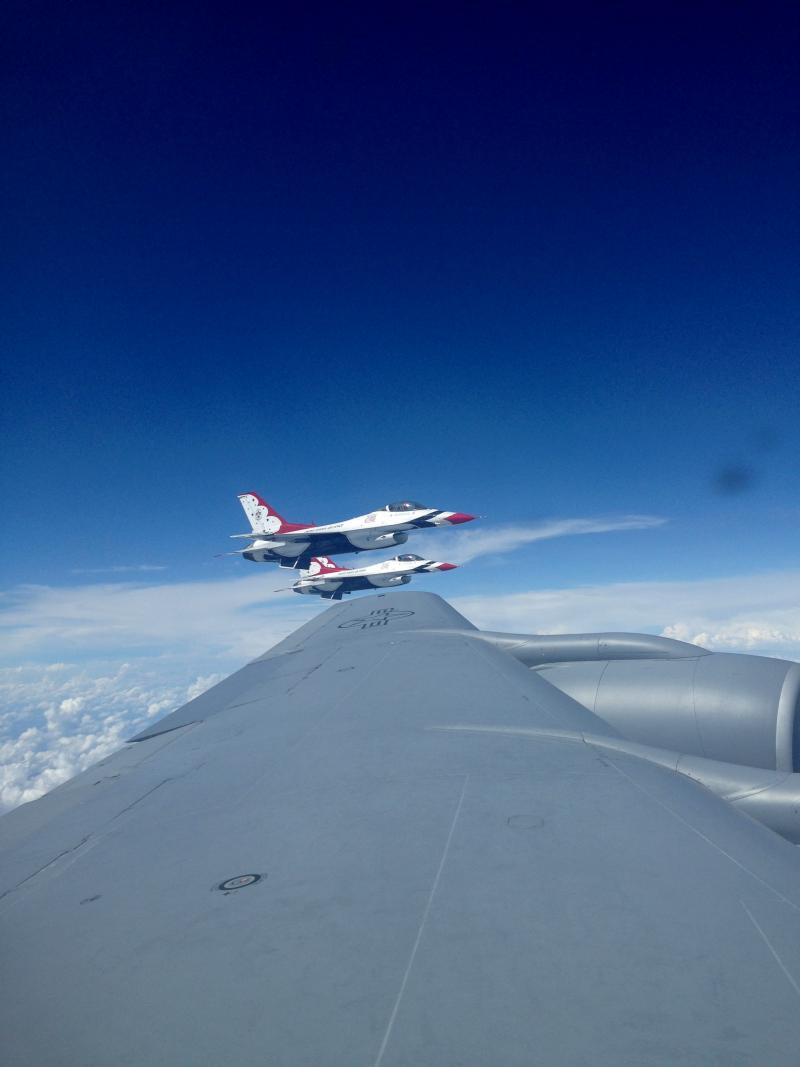 F-16 Thunderbirds fly near the wing of a KC-135 Stratotanker.