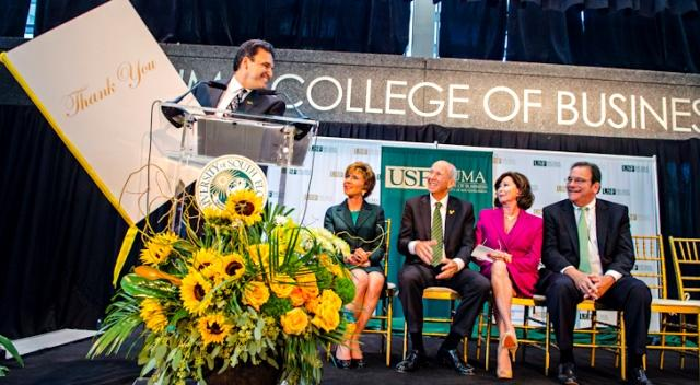 USF College of Business Dean Moez Limayem with a 'thank you' card for Les & Pam Muma (center, seated) at the College renaming ceremony October 10th.