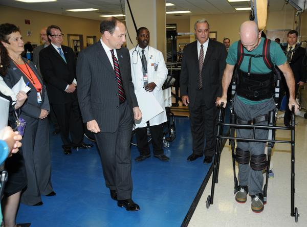 VA Secretary Bob McDonald (left) watches as paralyzed Navy Veteran Dwayne Scheuneman (right) demonstrates the Exoskeleton during the new leader's visit Wednesday at the James A. Haley VA Polytrauma Center.
