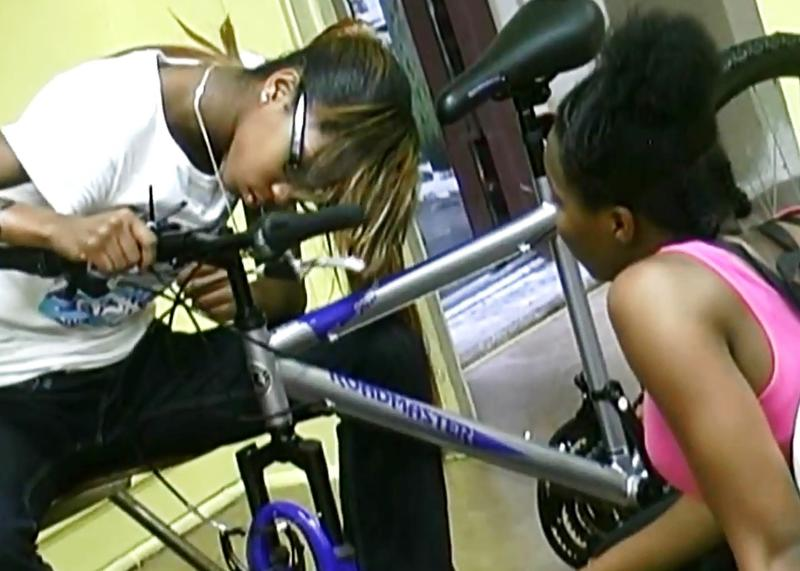 A scene from the Smart Bike video of teenagers learning to assemble bicycles.