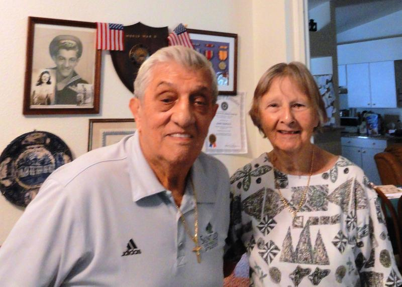 John and Joan Tedesco stand before a wall of World War II memorabilia including John's Navy photograph and military ribbons and medals.