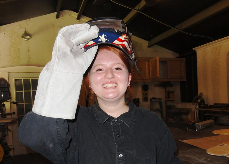 Cierra Grenier tries on her welder's helmet and gloves before her first lesson on the MIG welder.