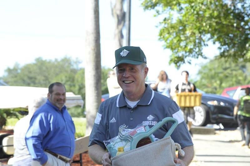 """Dr. William Lennox - the new president - helps carry a student's belongings to the dorm on """"Move-In Day"""" Thursday at Saint Leo University."""