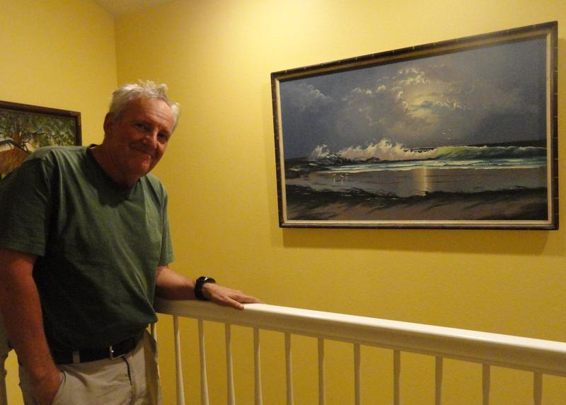 Jeff Klinkenberg poses next to a beach painting done by a Florida Highwaymen Artist.