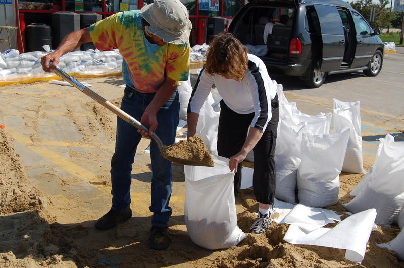Residents working together to fill sandbags in the parking lot of convenience store. Cedar Rapids, IA, June 11, 2008.
