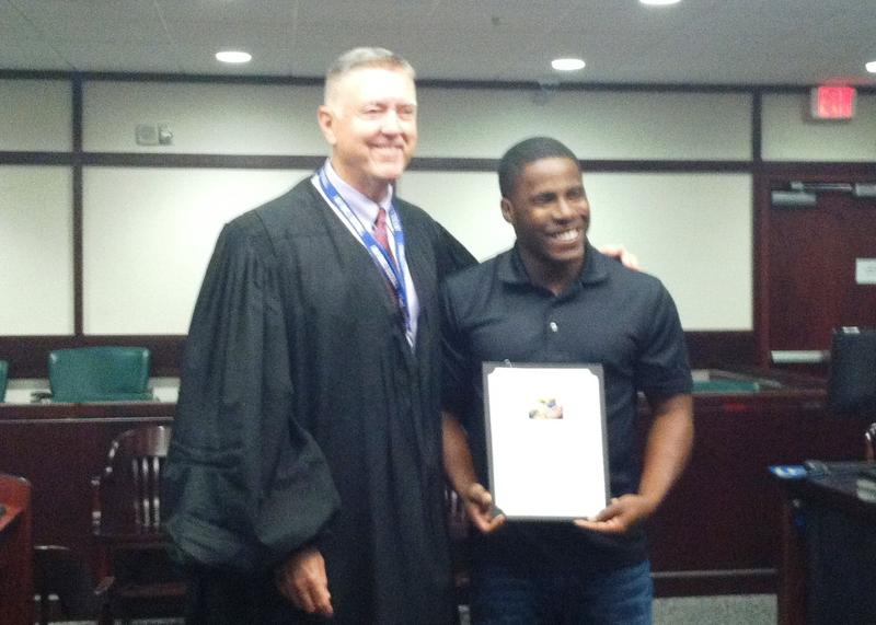 Hillsborough Circuit Judge Greg Holder poses with a graduate from the Veterans Treatment Court in August.