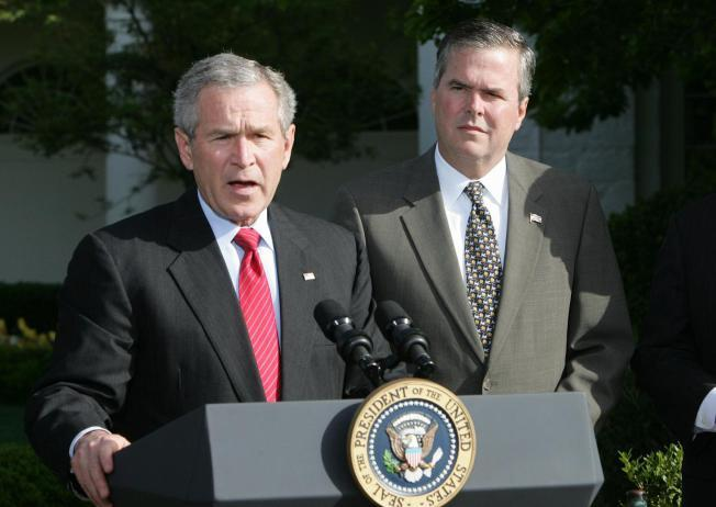 In this April 19, 2006 file photo, President George W. Bush, accompanied by his brother, then-Fla. Gov. Jeb Bush, speaks on the South Lawn at the White House in Washington.