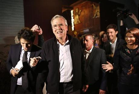 Jeb Bush walks with members of the media and supporters as he departs a campaign event held in a barn belonging to former .S. Sen. Scott Brown, R-Mass., Tuesday, Nov. 3, in Rye, N.H.