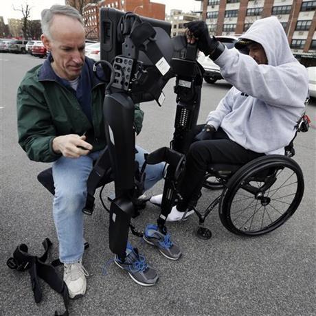 ReWalk Robotics service engineer Tom Coulter prepares a ReWalk device to allow paralyzed Army veteran Gene Laureano to walk Wednesday, Dec. 16, 2015, in Bronx, N.Y.