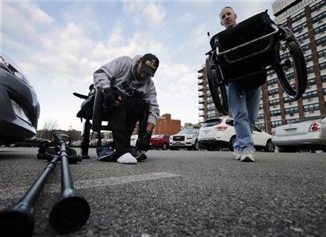 ReWalk Robotics service engineer Tom Coulter, right, moves paralyzed Army veteran Gene Laureano's wheelchair, as Laureano prepares to walk using a ReWalk device Wednesday, Dec. 16, 2015, in Bronx, N.Y.