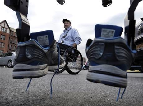 Paralyzed Army veteran Gene Laureano's sneakers are mounted on a ReWalk device as he prepares to use the machine to walk Wednesday, Dec. 16, 2015, in Bronx, N.Y.
