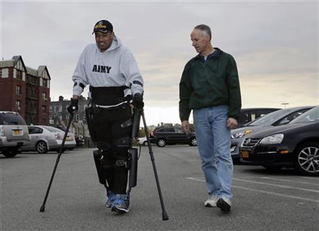 While ReWalk Robotics service engineer Tom Coulter, right, looks on, paralyzed Army veteran Gene Laureano smiles as he walks using a ReWalk device Wednesday, Dec. 16, 2015, in Bronx, N.Y.