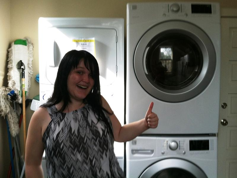 Athena Program case manager Morgan McKeown gives a thumbs up for the new washer and dryer donated to the residence for homeless women veterans.