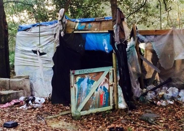 """A makeshift lean-to at one of the veterans' homeless camps. Note the """"keep out"""" message scrawled on the piece of wood."""
