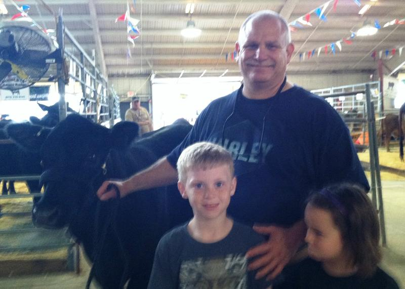 Albert Austrino and his 7-year-old-son Owen with the Angus cow he will show at the Florida State Fair.