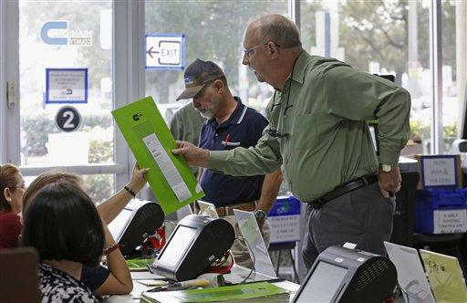 A voter receives his ballot his ballot as he prepares to cast his vote during early voting on Monday, Feb. 29 in Miami.