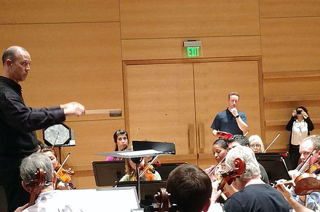 USF Conducting Master Class student Brent Douglas leads The Florida Orchestra as Michael Francis looks on.
