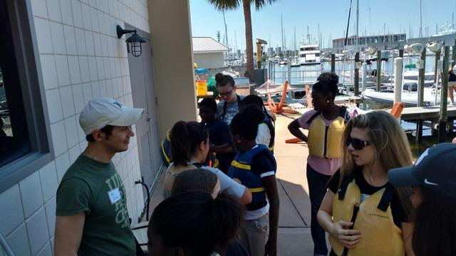 USFSP students talk with Fairmount Park teachers and volunteers while the fifth graders don their life jackets.