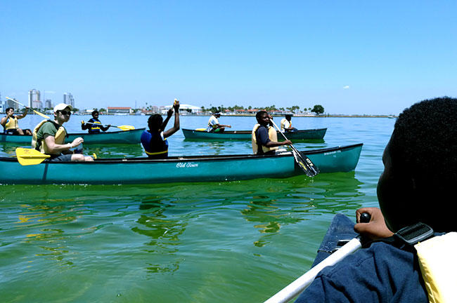 Fairmount Park Elementary School 5th grader Simeon Elias (right) paddles a canoe towards classmates and USF St. Petersburg students on Tampa Bay recently.