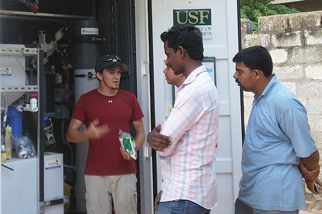 USF engineering graduate research assistant Robert Bair (left) explains the NEWgenerator to people in India.