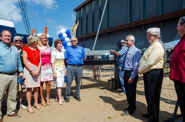 While officials from USF and FIO and local politicians look on, Duckworth Steel Boats owner Junior Duckworth (center, back) performs the ceremonial keel laying of the new research vessel.