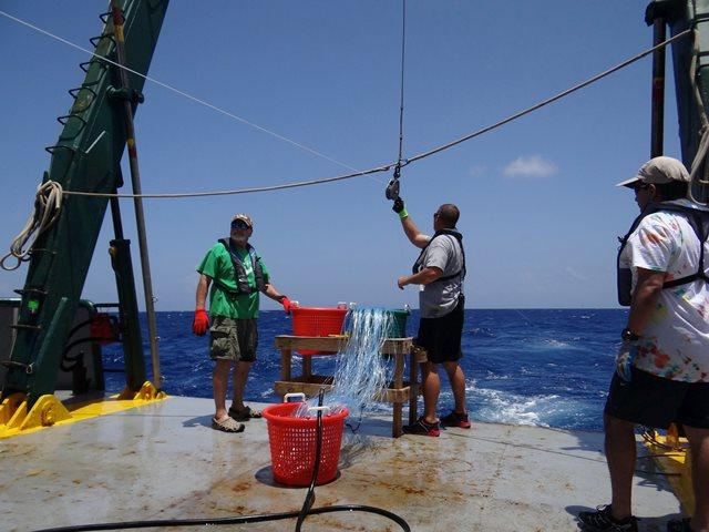 Crew members put the first hook of the expedition in the water.