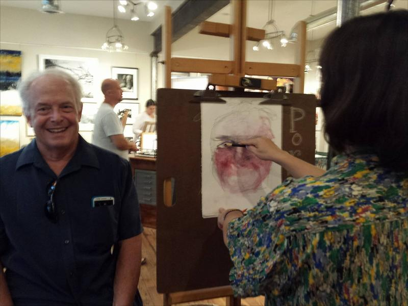 Robert McSweeney gets his portrait drawn by artist Eva Avenue.