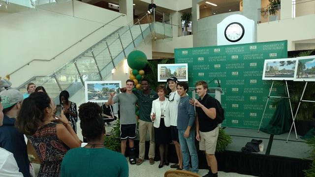 USF System President, Dr. Judy Genshaft, poses in front of renderings of The Village with students in the Marshall Student Center Thursday.
